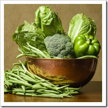 A Coper Bowl of Vegetables Containing Romanin Lettuce, Brocolli, Green Beans and a Green Pepper
